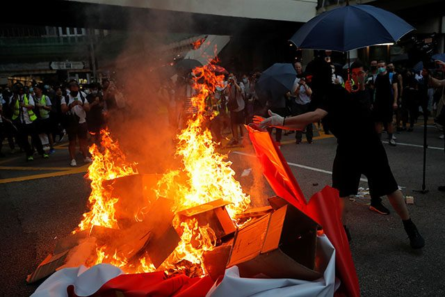 Hong Kong protesters burning a banner