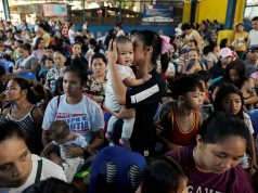 Mothers hold their children while waiting in line to receive free polio vaccine during a government-led mass vaccination program in Quezon City