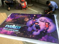 """A man takes down a promotional poster for the DreamWorks film """"Abonimable"""" which was being marketed in Vietnam as """"Everest: The Little Yeti"""" at a cinema in Hanoi,"""