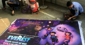 "A man takes down a promotional poster for the DreamWorks film ""Abonimable"" which was being marketed in Vietnam as ""Everest: The Little Yeti"" at a cinema in Hanoi,"
