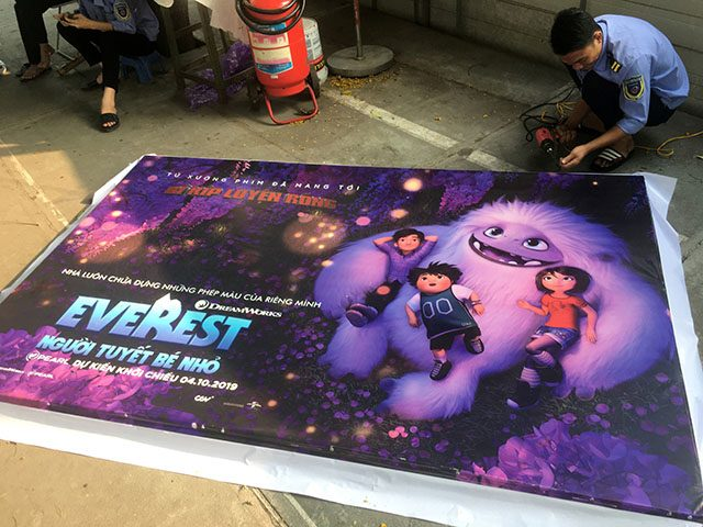 A man takes down a promotional poster for the DreamWorks film