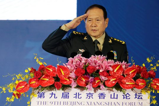 Chinese Defense Minister Wei Fenghe salutes before a speech at the Xiangshan Forum in Beijing