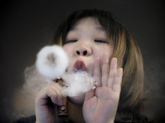 Saleswoman demonstrates vaping at Vape Shop in Beijing