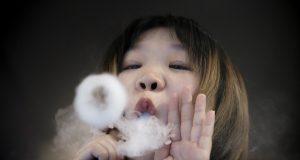 Saleswoman demonstrates vaping at Vape Shop in Beijing