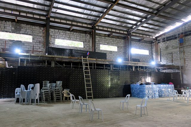 Chairs are stacked inside an unfinished structure, formerly the media centre for soccer at the Southeast Asian Games, in Rizal Memorial Stadium