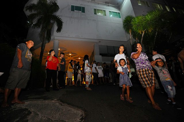 Visitors gather outside a hotel building following the earthquake that hit in Manado