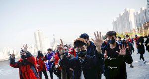 Hongkongers gesture as they chant slogans before a soccer match between Hong Kong and China outside Busan Asiad Stadium in Busan