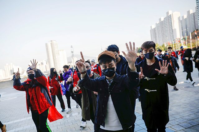 Hongkongers gesture as they chant slogans before a soccer match between Hong Kong and China outside Busan Asiad Stadium in Busan