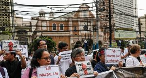Filipino activists hold placards calling for the end of Martial Law in Mindanao region during a rally held in observance of Human Rights Day in Manila