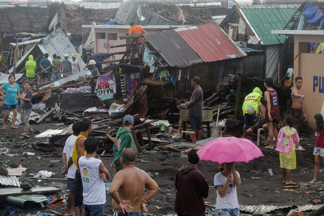 Residents stand among their damaged houses