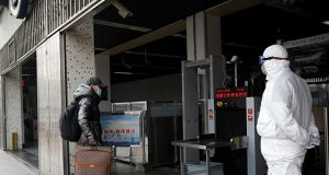 A worker in protective suit looks at a man while he enters the Xizhimen subway station, as the country is hit by an outbreak of the new coronavirus, in Beijing