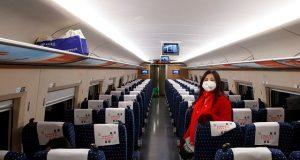 A woman wears a face masks as she travels on a high-speed train near Jiujiang