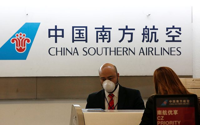 A China Southern Airlines employee wears a surgical mask as a preventive measure in light of the coronavirus outbreak in China, while he attends a customer behind the counter at Benito Juarez international airport in Mexico City