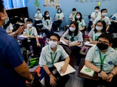 Students wear masks amid a health scare over a new virus that has infected thousands since emerging in China, in a Chinese school in Quezon City
