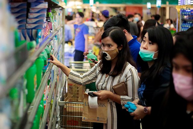 People hoard bottles of alcohol after the Philippine government confirmed the first case of the new coronavirus in the country, in Makati City