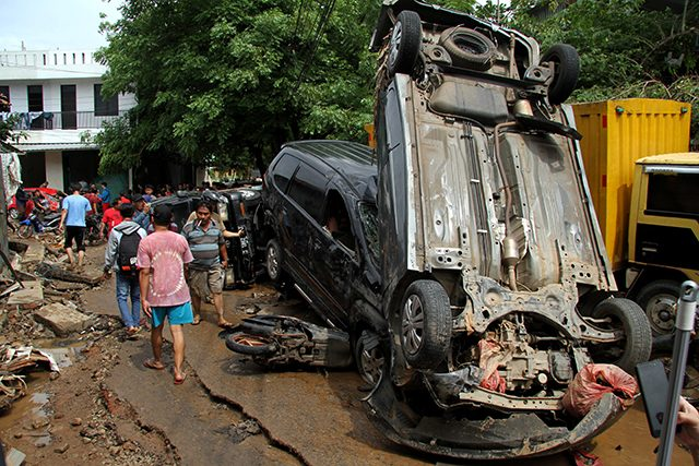 People pass vehicles damaged by floods after heavy rains in Bekasi, near Jakarta