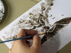Filipina artist Janina Sanico paints an image of Taal volcano