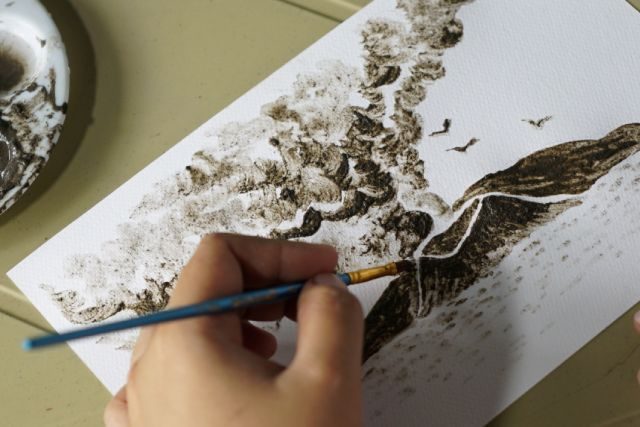 Filipina artist Janina Sanico paints an image of Taal volcano