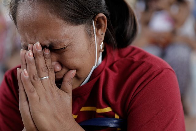 A woman displaced by Taal Volcano's eruption becomes emotional as she prays during a Catholic mass in an evacuation center
