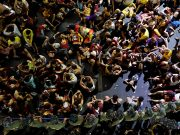 Filipino devotees rest in front of a police barricade as they wait for the statue of the Black Nazarene during its feast day at Quiapo in Manila