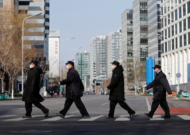 Security personnel wearing masks cross a road at the Financial Street in central Beijing