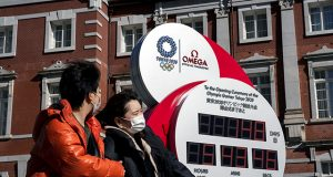 A couple wearing protective face masks, following an outbreak of the coronavirus, walk past the big Omega One-Year Countdown clock for the opening ceremony of the Tokyo 2020 Olympic outside of Tokyo Station in Tokyo
