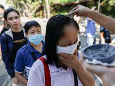 "Filipino Catholics wearing protective masks receive ash on top of their heads as the church observes a ""contactless"" Ash Wednesday amid coronavirus scare, at the National Shrine of Our Mother of Perpetual Help, Paranaque City"