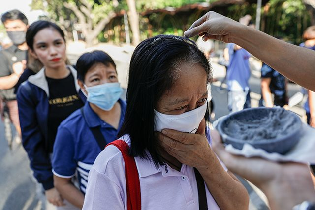 Filipino Catholics wearing protective masks receive ash on top of their heads as the church observes a