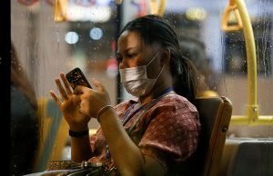 Person with mask using smartphone
